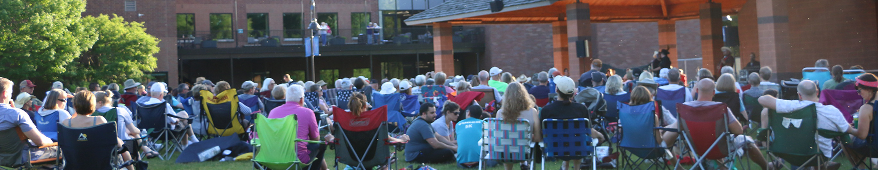 Summer concert at Shoreview Community Center with concert goers in folding chairs on the lawn